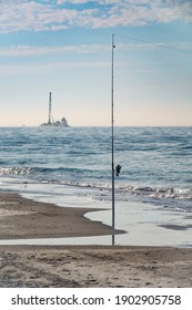 Fishing rod, upright on sandy beach along a barrier island, in view of offshore dredger with tower (maybe for mining sand for beach nourishment) in the Gulf of Mexico. An example of juxtaposition.