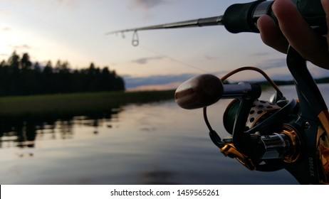 Fishing rod wheel closeup, beautiful lake and trees reflections in the lake