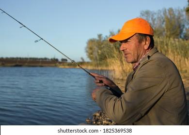Fishing rod wheel closeup, man fishing with a beautiful sunset.