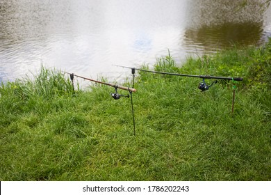 Fishing, fishing rods are on stands on the shore of the pond. Outdoor recreation, summer, vacation, day off