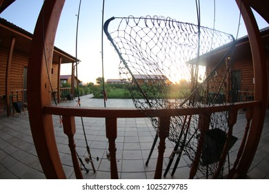 Fishing rods and podsachek on the base on the background of houses and the sun.