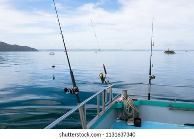 Fishing rods with reels on charter boat on tranquil day at sea in Far North District, Northland, New Zealand, NZ