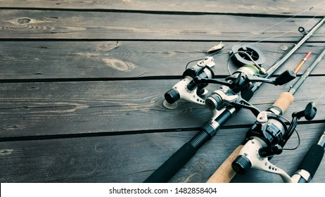 Fishing rods and reels on wooden background