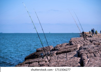 Fishing rods and reels in Port Aransas, Texas on popular jetty at the Gulf of Mexico with waves on the water.