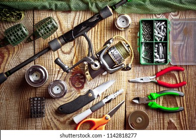 Fishing rods and spinnings in the composition with accessories for fishing on the old background on the table