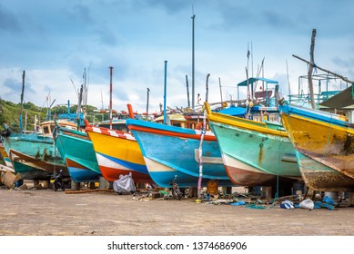 Fishing sea boats in a dry dock, Sri Lanka. Nice panorama of old wooden ships on a tropical shore. Ethnic traditional boats in a fishing port. Colorful trawlers under repair.