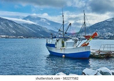 Fishing ship in harbor in city of Tromso with mountains in the background, Norway