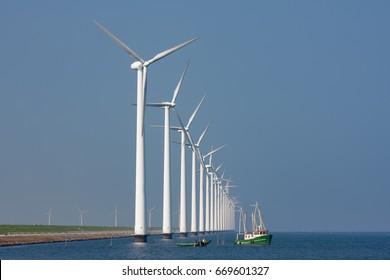 Fishing ship near a row af big wind turbines in the Dutch sea