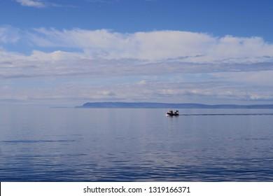 Fishing ship on vast blue, calm ocean, in front of mountainous coastline.