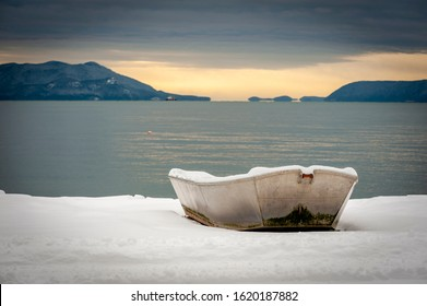 Fishing Skiff Covered With a Dusting of Snow. A small fishing boat pulled up on shore after a snowstorm in the Salish Sea area of western Washington state. Cypress and Orcas Islands in the background.