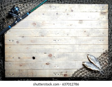 Fishing tackle and dried fish still-life on the wooden background.