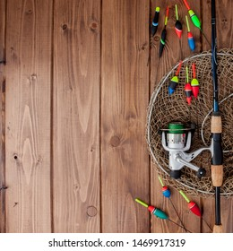 Fishing tackle - fishing rod fishing float and lures on beautiful blue wooden background, copy space.