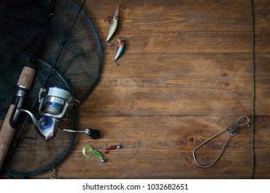 Fishing tackle - fishing spinning, hooks and lures on darken wooden background.Top view.