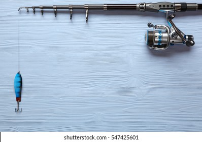 Fishing tackle - fishing spinning, hooks and lures on light wooden background.Top view.