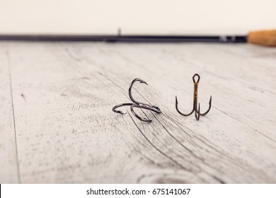 Fishing tackle - fishing spinning, hooks and lures on white wooden background.