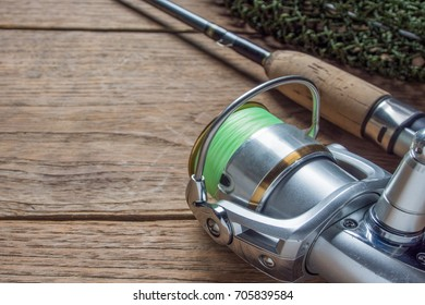 Fishing Tackle - spinning reel and rod on wooden background, Close up.