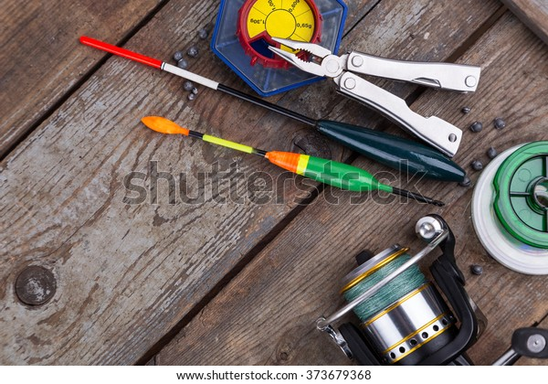 fishing tackles for anglers - swimmers, plummets and tools on wooden background