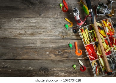 Fishing tackles background - fishing spinning and box with color fishing tackles on wooden boards. Top view. Copy space