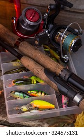 fishing tackles and fishing baits in box on wooden boards background