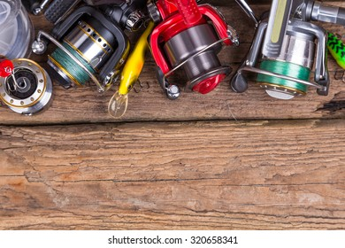 fishing tackles different rod and reel on timber board background. for design advertising or publication
