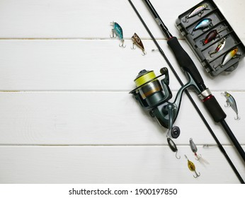 Fishing tackles lay on white wooden boards. Set of fishing tackles. Top view on spool, rod, spoons, wobblers and lure box.