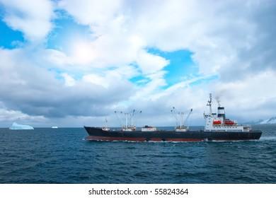Fishing trawler in Atlantic ocean near icebergs
