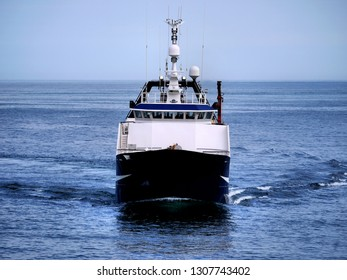 Fishing Trawler underway at sea in calm waters to fishing grounds.