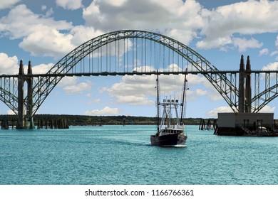 Fishing troller passes under the Yaquina Bay Bridge  to enter the harbor at  Newport, Oregon