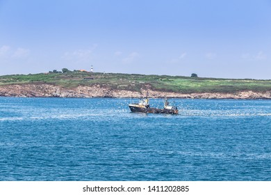 Fishing vessel getting back to the Sozopol pier from the Black sea,full with fish,Fishing boat returning with lots of seagulls feeding at the rear of the boat,Sozopol Bulgaria,May 29 2019