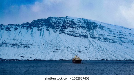 Fishing vessel in the ocean with a snow covered mountain behind it