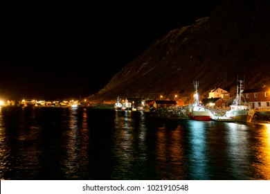 Fishing vessels docket in the small village of Ballstad in Lofoten. Night scenery of the harbor.