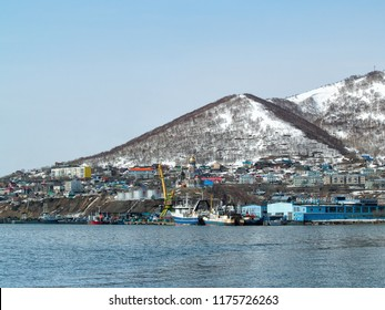 Fishing vessels stand near the shore in Avacha Bay at the foot of snow-covered hills in winter in Petropavlovsk-Kamchatsky, Russia