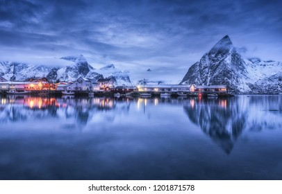 Fishing village with boats at night, Lofoten islands, Norway. Winter landscape with buildings, illumination, snowy mountains, sea, purple cloudy sky reflected in water at dusk. Norwegian rorbuer