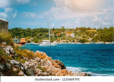 Fishing village Fiskardo, Kefalonia Island Greece. White catamaran leave harbor put out to sea on sunny summer day