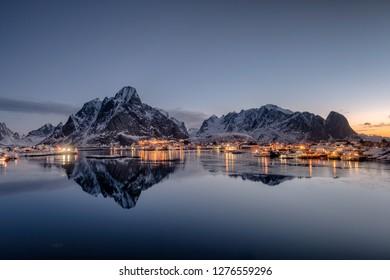 Fishing village illumination with mountain range  reflection on coastline at dawn. Lofoten islands, Norway
