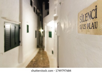 """Fishing village of Menorca at night. Poster says """"silence please"""" (balearic islands, spain)"""