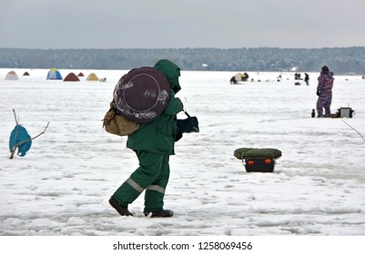 Fishing in the winter. A fisherman with a set of items for fishing, goes through the pond to find a place to catch fish. The ice is covered with snow and trampled by footprints. In the distance you ca