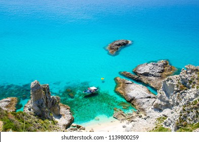 Fishing yacht with shadows on bottom sail drift and rubber boat park in lagoon blue azure turquoise water surface of sea among rocks not far from cape Capo Vaticano Ricadi, Calabria, Southern Italy