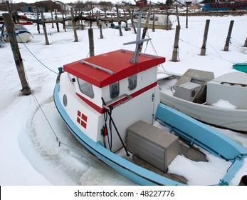 Fishingboat in frozen marina.