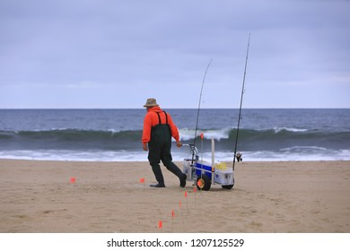 A fishman is walking by the ocean coast with package of fishing rods.