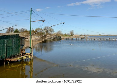 fishnet of old traditional stilt fishing hut on the lagoon, shot in bright spring sun light at Comacchio, Ferrara,  Italy