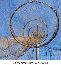 Fishnets seen from the inside drying in the air while hanging at a long pole