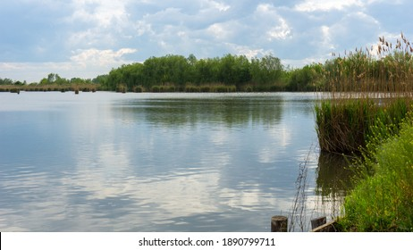 Fishpond, Biharugra - The picture shows the sky reflected on the water surface. The water is surrounded by reeds. Biharugra, Bekes county, Hungary, May 2020, bekesstock, csabaprog
