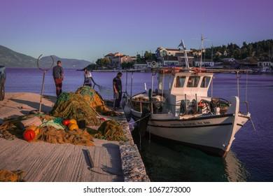 Fiskardo, Greece - April 30, 2016, Fishermen on  pier of  town of Fiscardo on island of Kefalonia in Greece
