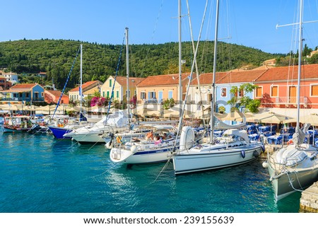 FISKARDO PORT, KEFALONIA ISLAND, GREECE - SEP 19, 2014: Yacht boats on blue sea and view of Fiskardo fishing village with port. Yachting is a popular activity on Greek islands.
