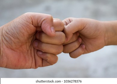 Fist bump between the kid and his parent with an eye level angle