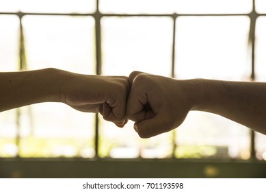 Fist bump together to show confidence and mutual acceptance.