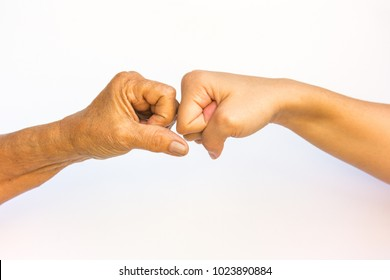 Fist bump of two generation, old against the young one, on white background.