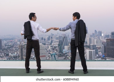 Fist Bumping Corporate Colleagues Teamwork between professional Couple businessman over the cityscape background at evening time, Business success concept