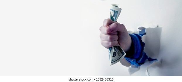 Fist full of paper money dollars, punching through a wall as symbol of purposefulness and desire to be rich